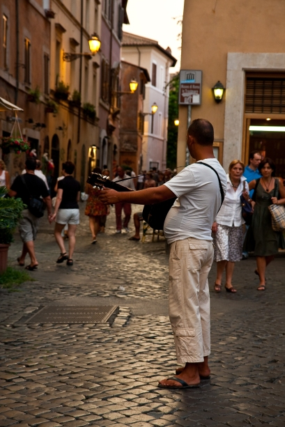 Playing his guitar in front of a restaurant.